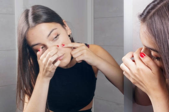Young Woman Squeezing Pimple